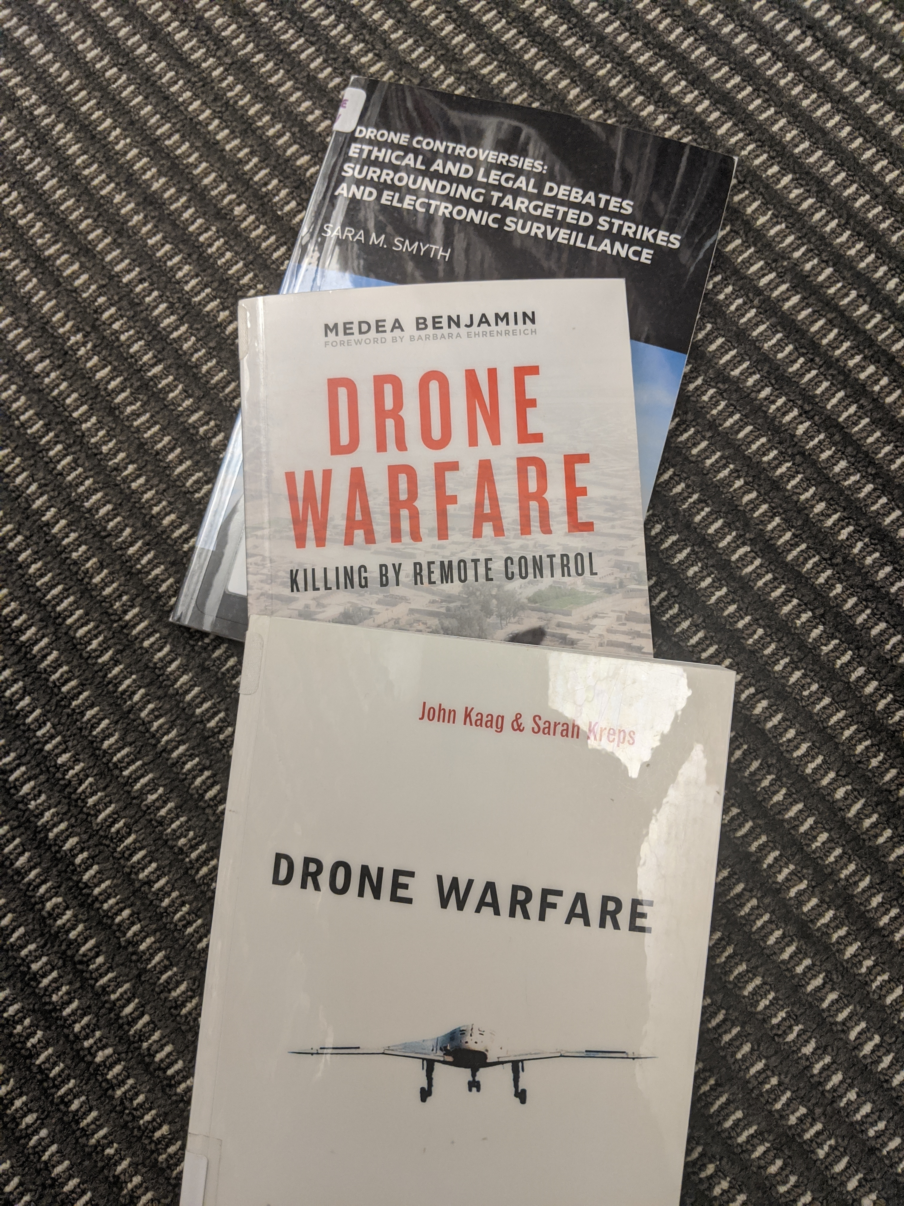 Three books. Titles: Drone Controversies: Ethical and Legal Debates Surrounding Targeted Strikes and Electronic Surveilance, Drone Warfare: Killing by Remote Control, Drone Warfare