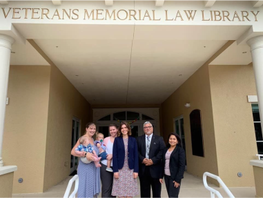 Five adults and two babies under a Veterans Memorial Law Library sign