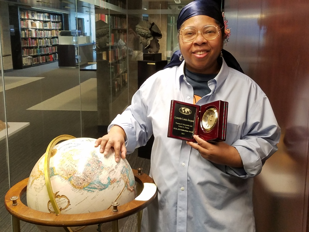 Lyonette Louis-Jaques holding her award while standing next to a large globe in a library.